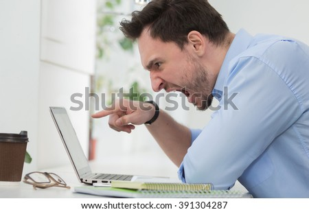 Happy male freelancer communicating with friend abroad using laptop computer. Handsome man having break during work.