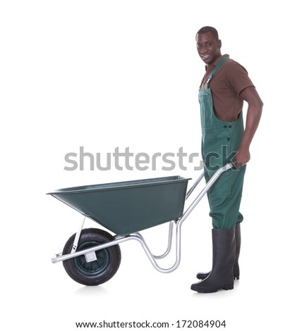 Happy Male Gardener Holding Wheelbarrow Over White Background - stock photo