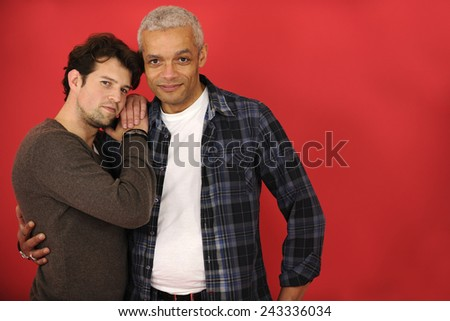 Happy male gay couple in love on red background with copyspace