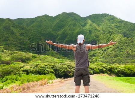 Happy male hiker with arms outstretched surrounded by a beautiful mountain setting.   - stock photo