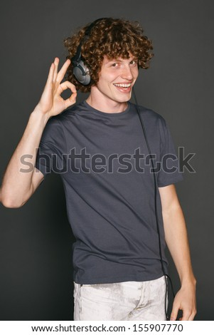 Happy male in headphones gesturing OK sign, against gray background - stock photo