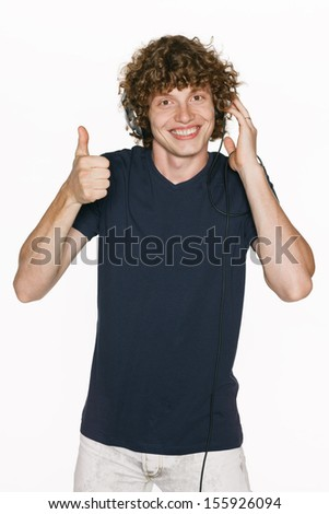 Happy male in headphones gesturing thumb up, against white background - stock photo