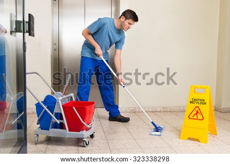 Happy Male Janitor With Cleaning Equipments Mopping Floor - stock photo