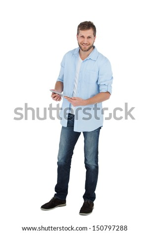 Happy male model using his tablet pc on white background - stock photo