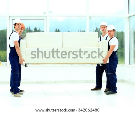 happy male movers in uniform carrying white sofa - stock photo