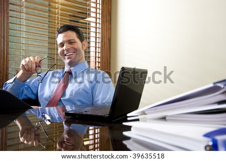 Happy male office worker sitting with laptop computer on table