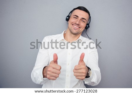 Happy male operator in headphones showing thumbs up over gray background. Looking at camera - stock photo
