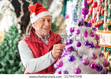 Happy male owner decorating Christmas tree with balls at store - stock photo