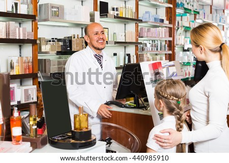 Happy male pharmacist wearing white coat standing at the counter in pharmacy  - stock photo