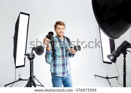 Happy male photographer standing in photo studio with equipments - stock photo