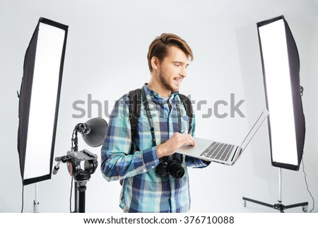 Happy male photographer using laptop computer in photo studio with eqipments - stock photo