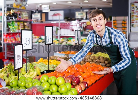 happy male seller posing with apples, tangerines and bananas in store