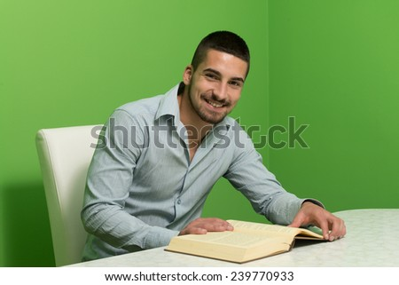 Happy Male Student Reading A Book - Green Background