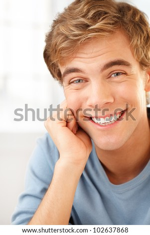 happy male student smiling indoors - stock photo