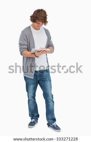 Happy male student using a touch pad against white background - stock photo