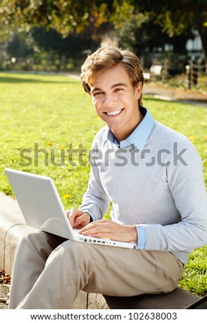 happy male student using laptop outdoors