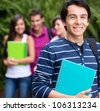 Happy male student with a group of people at the background - stock photo