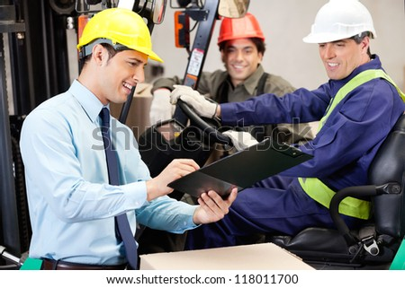 Happy male supervisor communicating with forklift driver and foreman at warehouse - stock photo