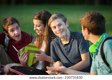 Happy male teen sitting with students outdoors - stock photo