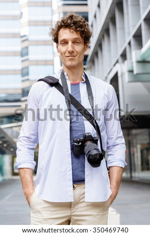 Happy male tourist in casual clothes in city with camera