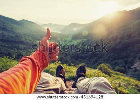 Happy male traveler showing thumb up in summer mountains at sunset, point of view shot - stock photo