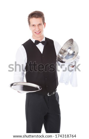 Happy Male Waiter Opening Cloche Lid Cover Over White Background - stock photo