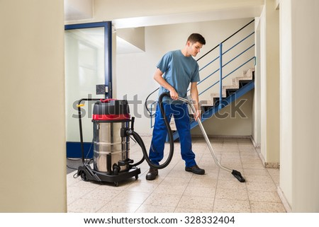 Happy Male Worker Cleaning Floor With Vacuum Cleaner Appliance - stock photo