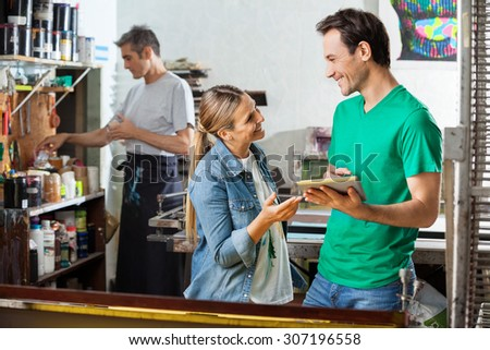 Happy male worker holding digital tablet while looking at female colleague in paper factory - stock photo