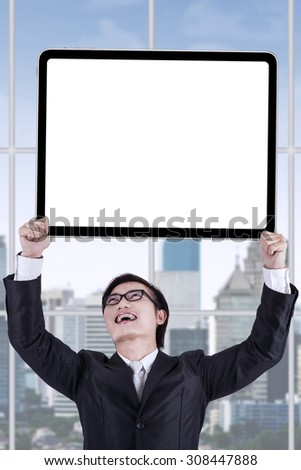 Happy male worker with formal suit, holding an empty billboard in the office - stock photo