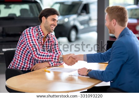 Happy man an buying a car in dealership they are shaking hands to close the deal - stock photo