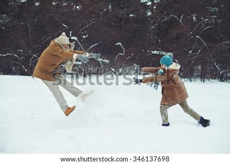 Happy man and his son playing in snowdrift - stock photo