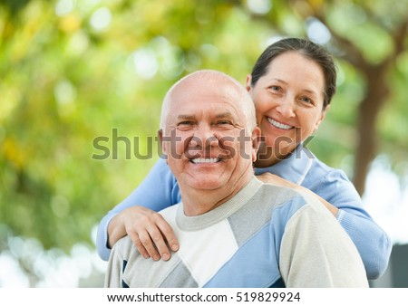 Happy man and smiling woman together against blured trees of park or forest