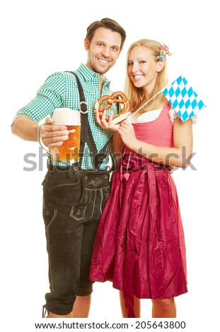 Happy man and smiling woman with beer and pretzel at Oktoberfest in Bavaria - stock photo