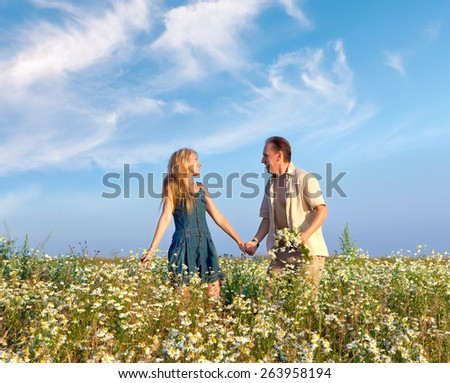 Happy man and the woman  in the field with camomiles - stock photo