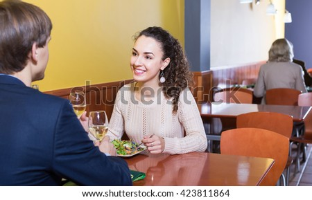 Happy man and woman chatting as having date in restaurant