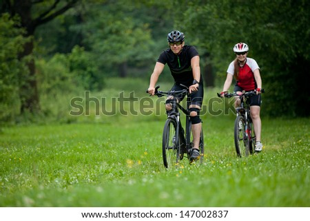 happy Man and woman exercising with bicycles outdoors, they are a couple in forest