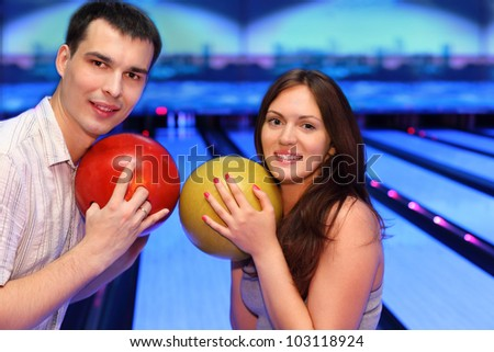 Happy man and woman hold balls and look at camera in bowling - stock photo