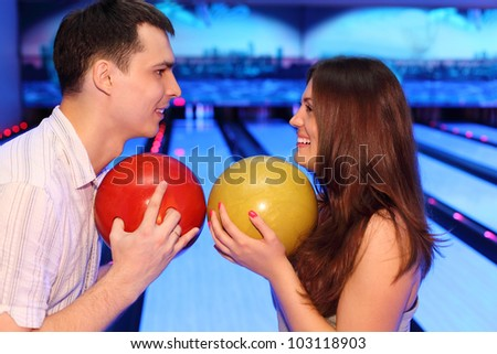 Happy man and woman hold balls and look at each other in bowling