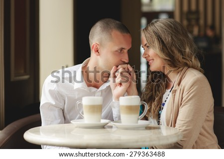 Happy man and woman in cafe. Loving couple on date at cafe. Two people in cafe enjoying the time spending with each other. Couple in cafe drinking coffee latte and smiling. Happy couple - stock photo
