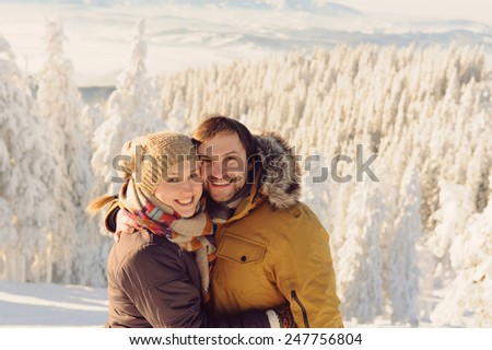 happy man and woman in snowy mountains - stock photo