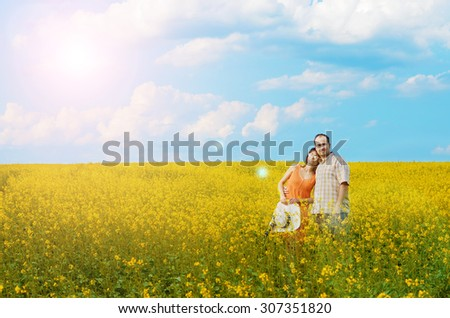 Happy man and woman in yellow meadow at summer
