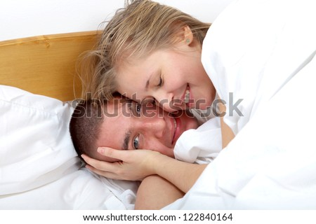 Happy man and woman laying in bed smiling and loving each other.
