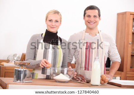 Happy man and woman preparing a cake - stock photo