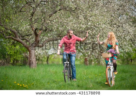 Happy man and woman riding bicycles in the blooming spring garden and giving each other a high five. Female with long blond hair wearing flowered dress and man in a red shirt and jeans. Front view