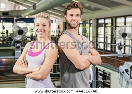 Happy man and woman standing with arms crossed at gym