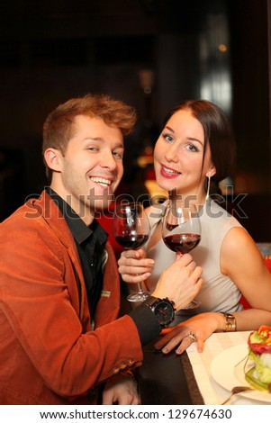 Happy man and woman with a glass of wine watching the camera - stock photo