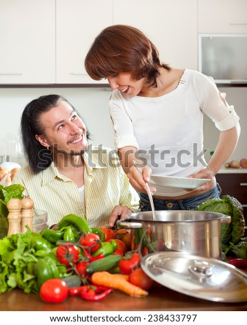 Happy man and woman with vegetables in kitchen at home