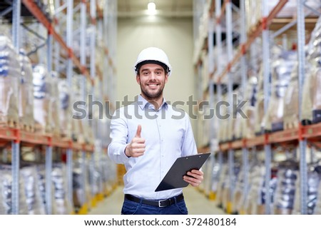 happy man at warehouse showing thumbs up gesture - stock photo