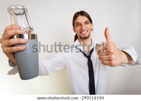 Happy man bartender with shaker making alcohol cocktail drink thumb up gesture studio shot on gray