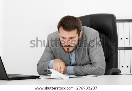 happy man businessman at his desk makes a paper airplane